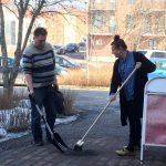Kaksi henkilöä siivoamassa pihaa.