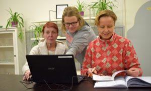 Kolme henkilöä tietokoneen ääressä Klubitalolla.