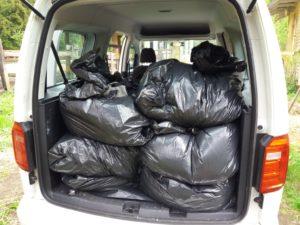 Klubitalon auto on pakattu täyteen jätesäkkejä, joissa on hevosen lantaa kasvimaalle vietäväksi.